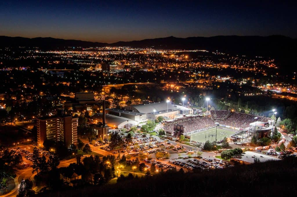 A packed Washington Grizzly Stadium and the lights of Missoula as seen from Mt. Sentinel.