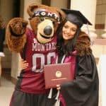 Sahar Qasem Muthna hugs Monte while holding her diploma from UM.
